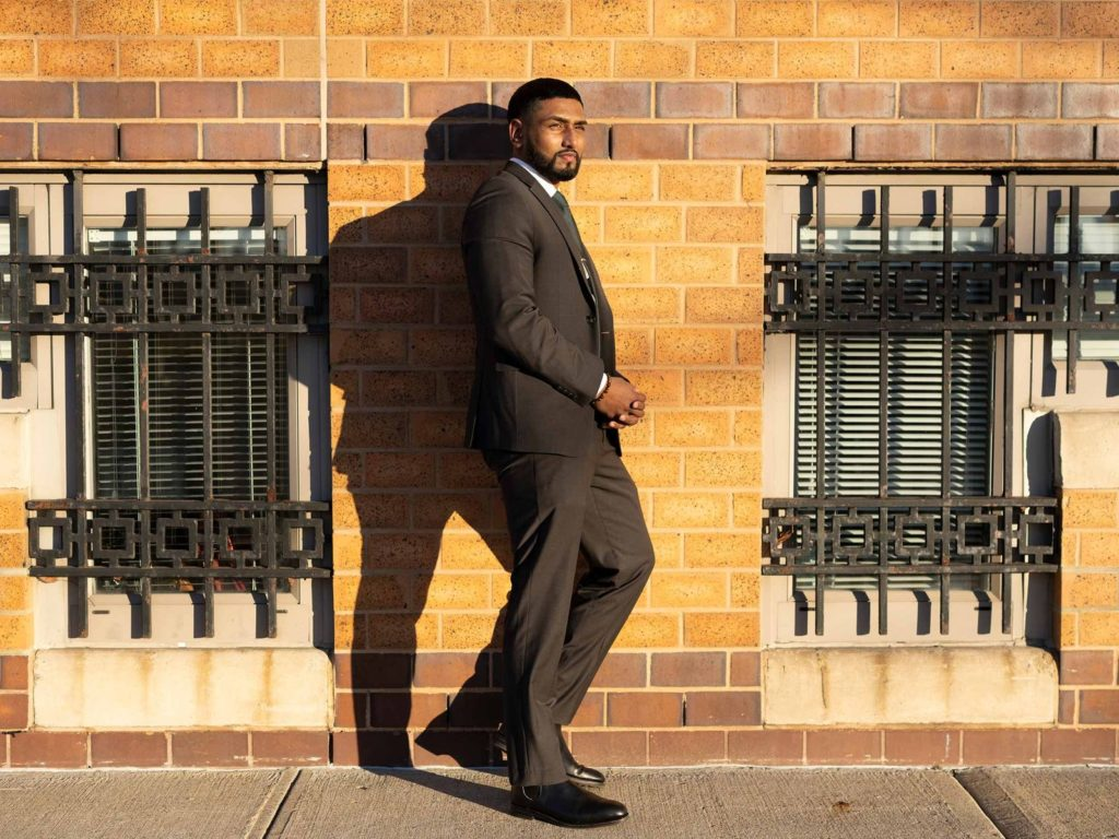 Kris Sidial, MCIT Online Student, wearing a suit, stands against building on a New York City sidewalk.