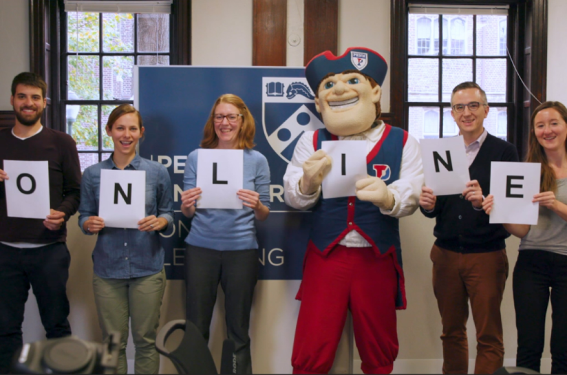 """Penn Engineering staff and faculty members posing with the Penn Quaker holding up signs that spell out """"ONLINE."""""""